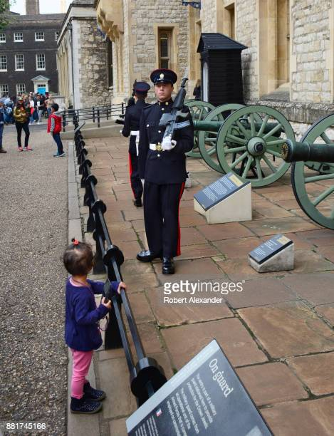 A young girl watches as armed sentries man their posts in the Tower of London complex in London England The sentries are a part of a military guard...