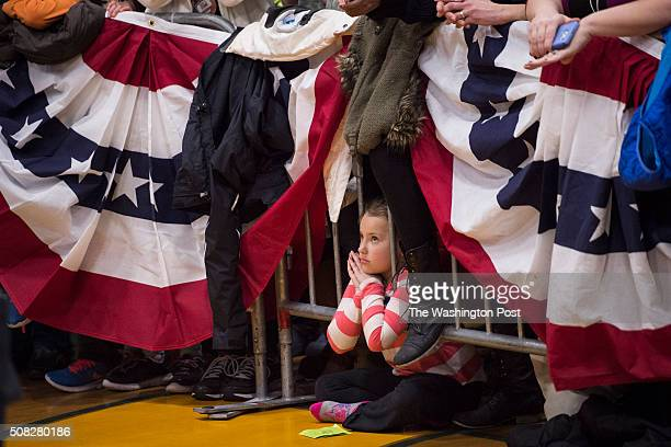 A young girl watches as democratic presidential candidate Hillary Clinton speaks to supporters during a Manchester GOTV organizing event with Gabby...
