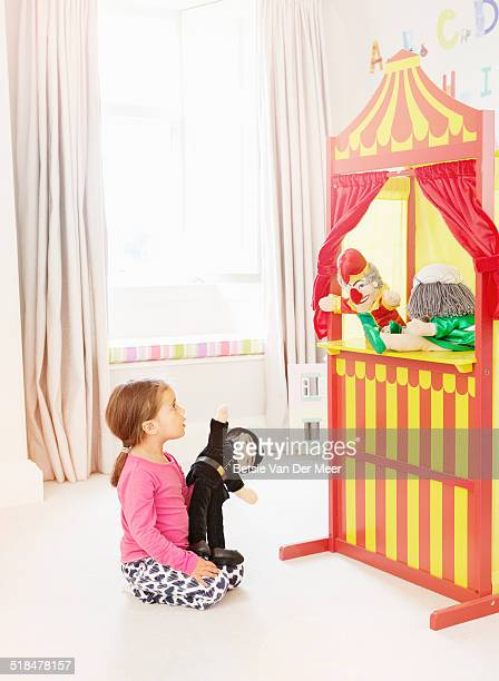 young girl watches punch and judy puppet show. - puppet show stock photos and pictures