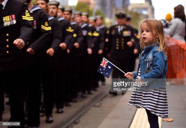 A young girl watches sailors march during the Anzac Day parade in Melbourne on April 25 2018 Tens of thousands of Australians and New Zealanders...
