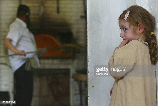 A young girl watches UltraOrthodox men prepare matzoh a traditional handmade unleavened bread for Passover in a bakery April 20 2005 in Kfar Habad...