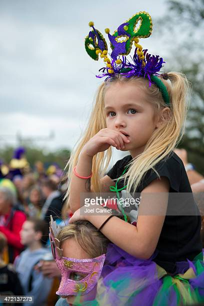 young girl watching mardi gras parade - mardi gras parade stock photos and pictures