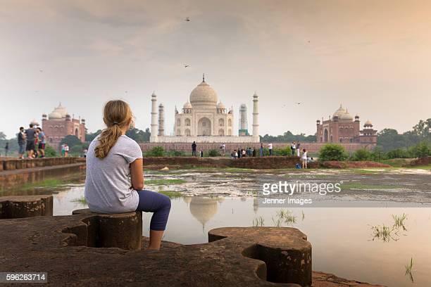 A young girl watching The Taj Mahal at sunset.