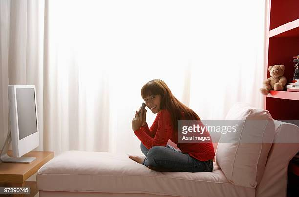 young girl watching TV in her bedroom