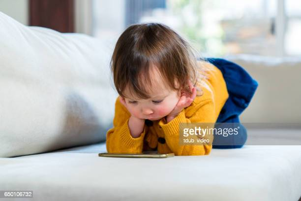 young girl watching tv on a smartphone - tdub_video stock pictures, royalty-free photos & images
