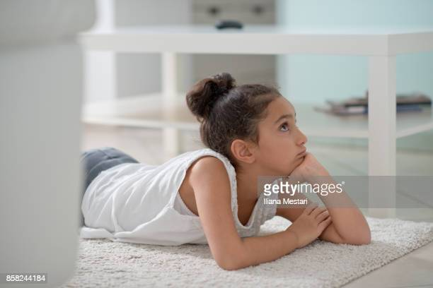 Young girl watching tv on the floor