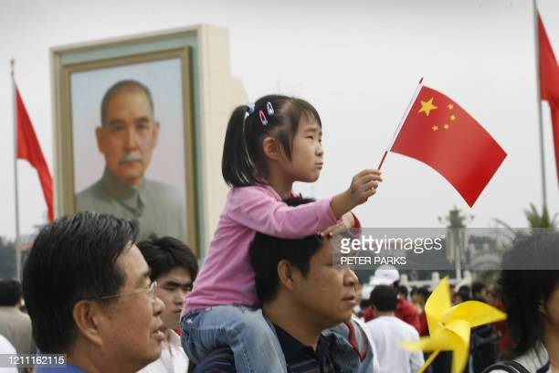 A young girl waves a Chinese flag in front of a giant portrait of the founder of modern China Sun Yatsen on Tiananmen Square in Beijing 01 October...