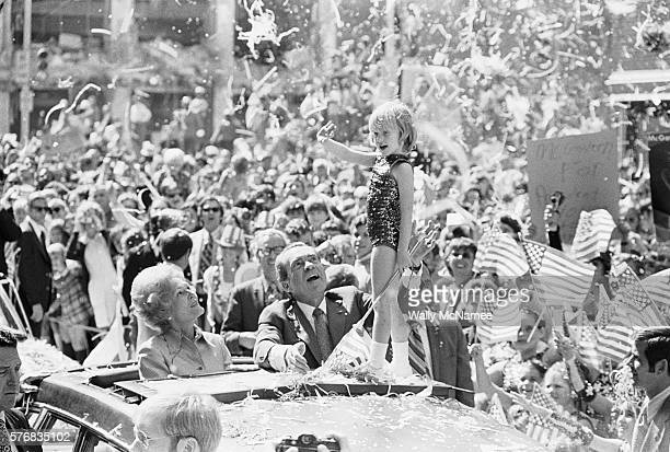 A young girl waves from the top of the presidential limousine as confetti and streamers rain down on Peachtree Street during President Richard Nixon...