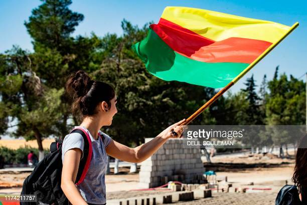 A young girl waves the flag of Kurdistan during a demonstration by Syrian Kurds against Turkish threats to launch a military operation on their...