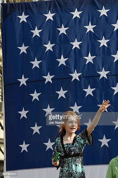 A young girl waves to Democratic presidential hopeful US Senator Hillary Clinton during a campaign rally at the corner of South Beaver and West...