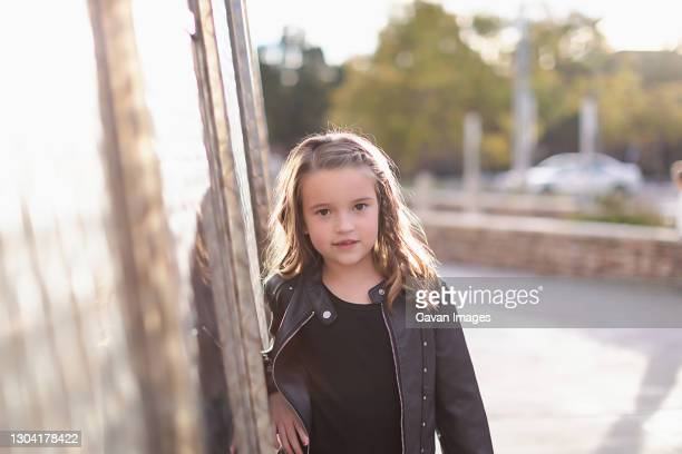 young girl wearing a black leather jacked leaning on metal wall - silver boot stock pictures, royalty-free photos & images