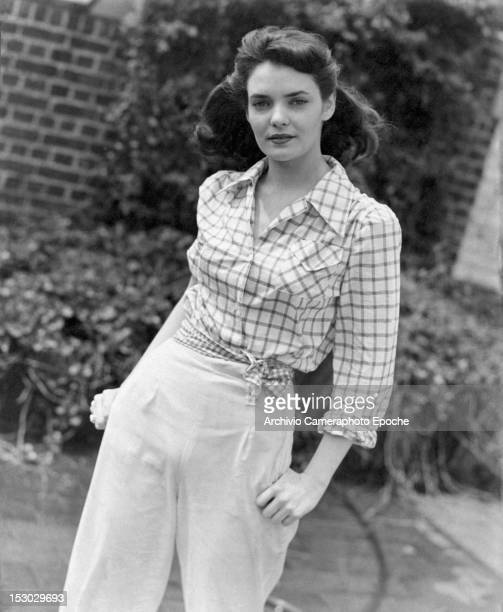 A young girl wearing a checkered shirt and a pair of trousers circa 1948