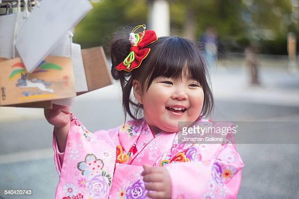 Young girl wearing a kimono placing her prayer