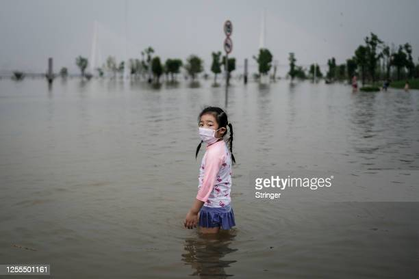 Young girl, wearing a mask, plays in the flooded Jiangtan park caused by heavy rains along the Yangtze river on July 10, 2020 in Wuhan, China. Wuhan...