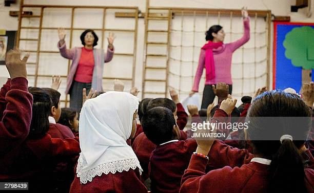 WITH 'RELIGIOUS EDUCATION A FESTIVAL OF LIGHT IN BRITAIN' A young girl wearing a muslim headscarf listens as two teachers instruct the class in...