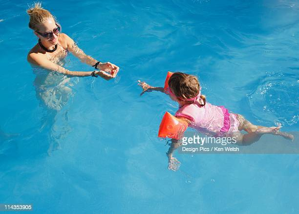 A Young Girl Wearing A Personal Floatation Device Vest And Armbands To Practice Swimming In A Pool With Her Mother