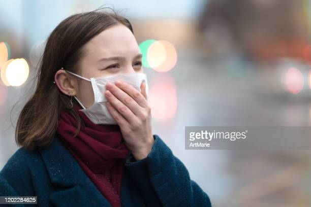 young girl wearing a protective face mask - mascherina chirurgica foto e immagini stock