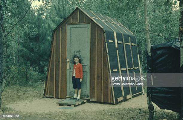 Young girl wearing a red jacket standing near the door of an outhouse under construction 1966