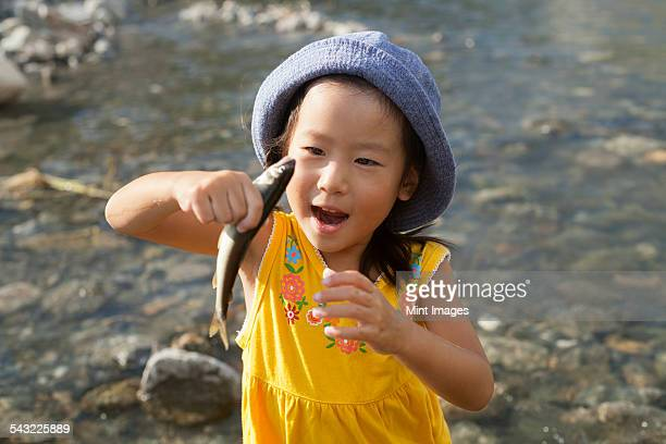 young girl wearing a summer hat, holding a fish. - 夏休み ストックフォトと画像