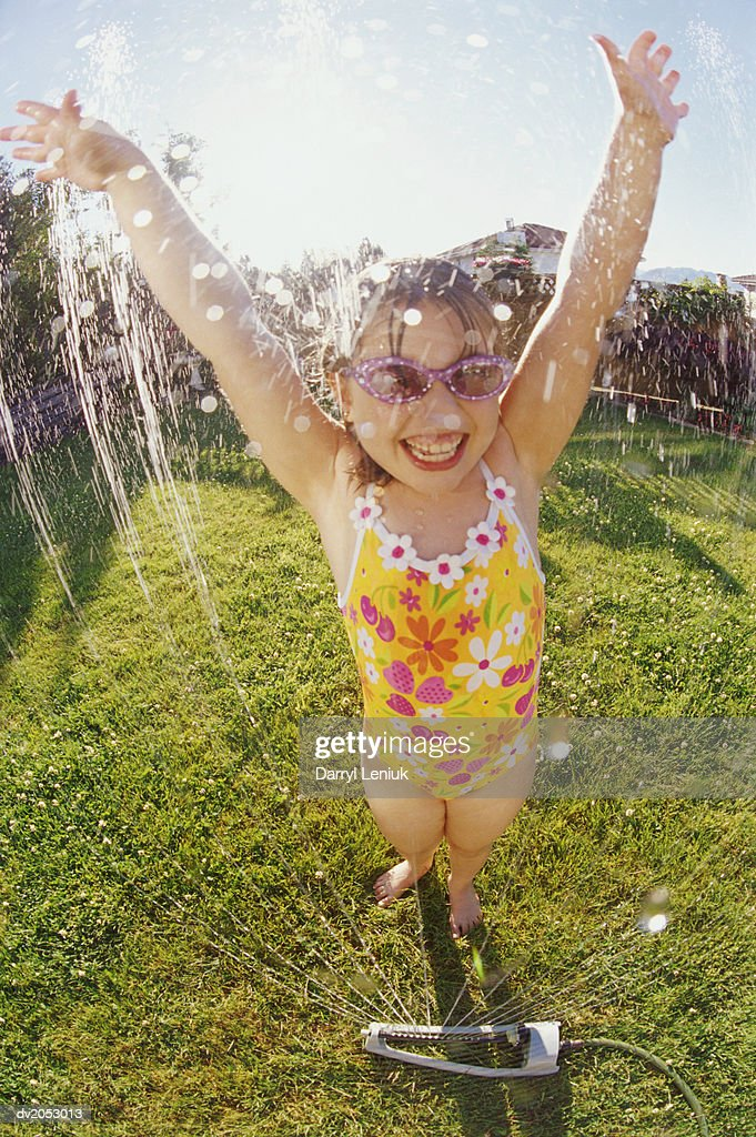 Young Girl Wearing a Swimming Costume, Being Sprayed with Water From a Garden Sprinkler : Stock Photo