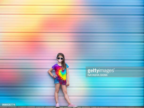 young girl wearing a tie dye shirt posing in front of a garage wall - multi colored shoe stock pictures, royalty-free photos & images