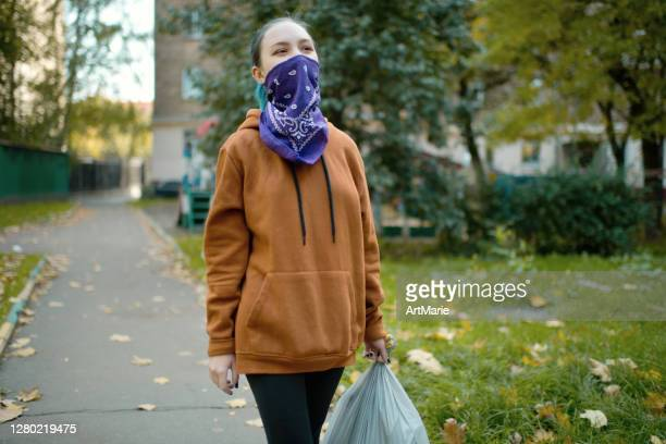 バンダナを覆う代替顔を身に着けている若い女の子はゴミを投げるつもりです - ゲートル ストックフォトと画像