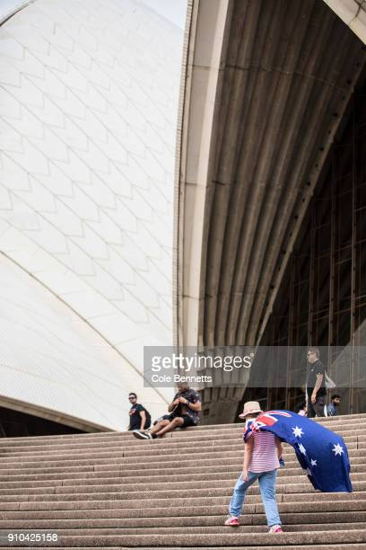 A young girl wearing an Australia flag as a cape walks up the stairs to the Opera House on January 26 2018 in Sydney Australia Australia Day formerly...