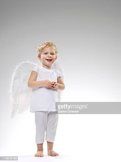 Young girl wearing angel wings.