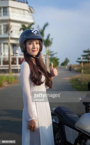 Young girl wearing ao dai with helmet on showing number one hand standing beside motobike
