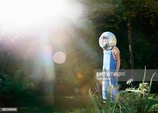 young girl wearing astronaut helmet