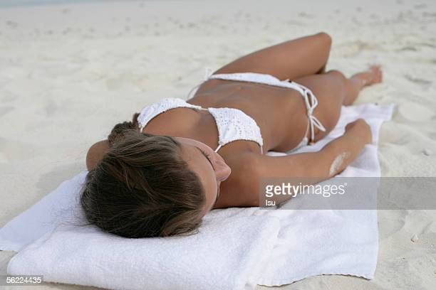 Young girl wearing bikini lying at the beach, Maldives