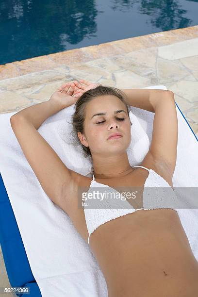 Young girl wearing bikini, lying on towel at swimming pool, sleeping