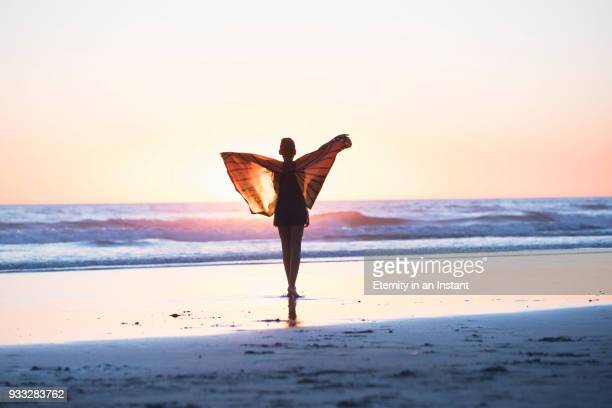 Young girl wearing butterfly wings and dancing on the beach at sunset