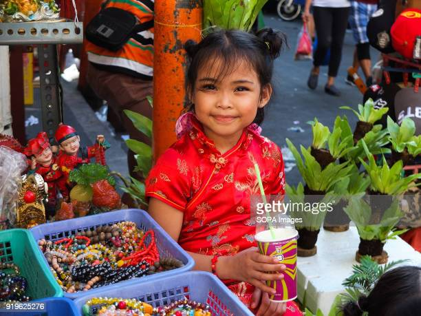 CHINATOWN MANILA PHILIPPINES A young girl wearing cheongsam a traditional chinese dress for women smiles while quenching her thirst Filipinos...