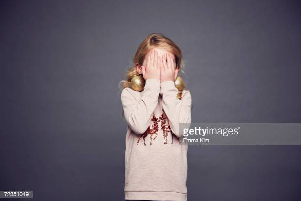 Young girl wearing Christmas jumper and bauble earrings, covering face with hands