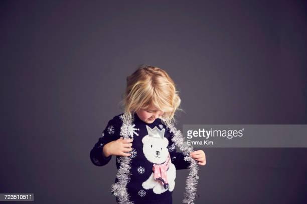 young girl wearing christmas jumper and tinsel around neck - christmas jumper fotografías e imágenes de stock