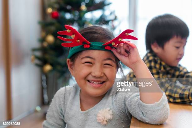 Young girl wearing Christmas reindeer antlers smiling at the camera