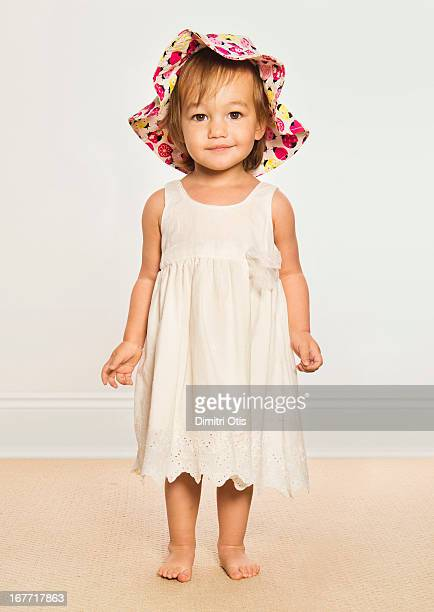 Young girl wearing colourful hat, smiling