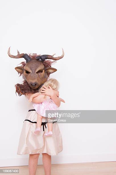 Young girl wearing deer a mask, holding doll