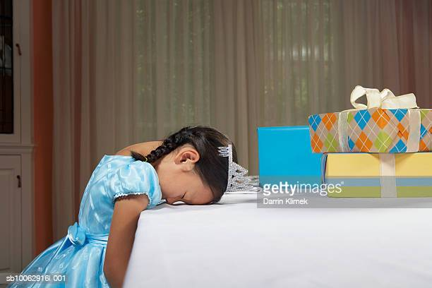 Young girl (6-7 years) wearing dress and tiara, sleeping with head on table by birthday present