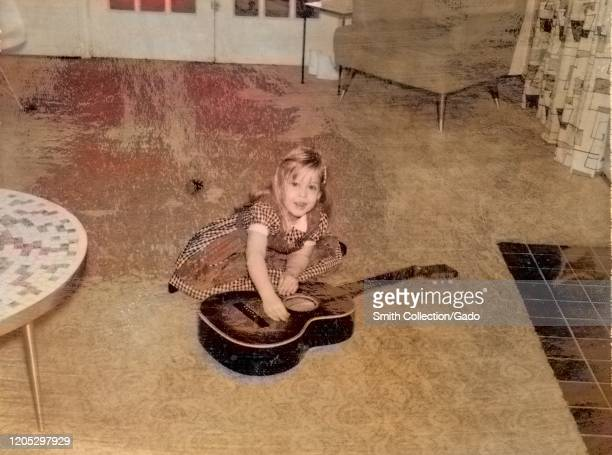Young girl wearing dress, strumming and pretending to play a guitar which lies on the floor of a suburban living room, with coffee table, chair and...