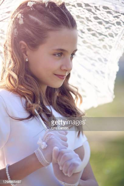 young girl wearing first communion dress outdoors with umbrella - cris cantón photography fotografías e imágenes de stock