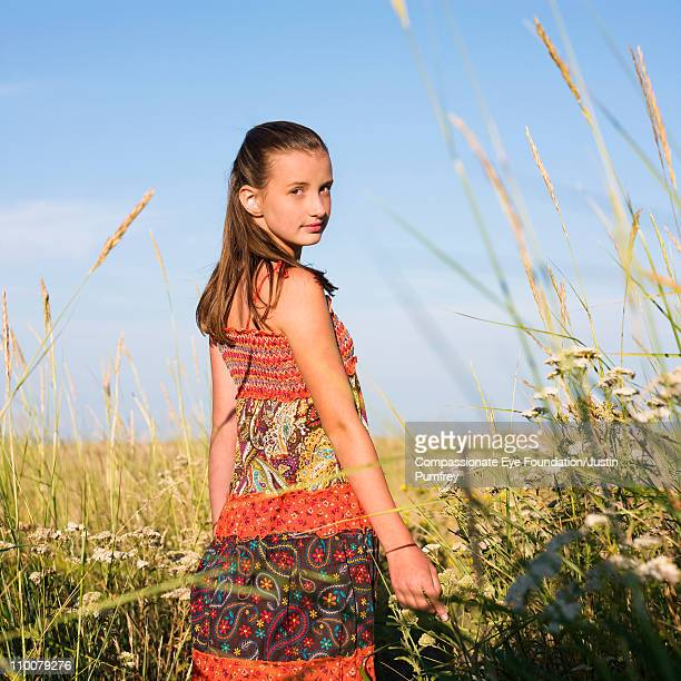 "young girl wearing floral dress in tall grass - ""compassionate eye"" fotografías e imágenes de stock"
