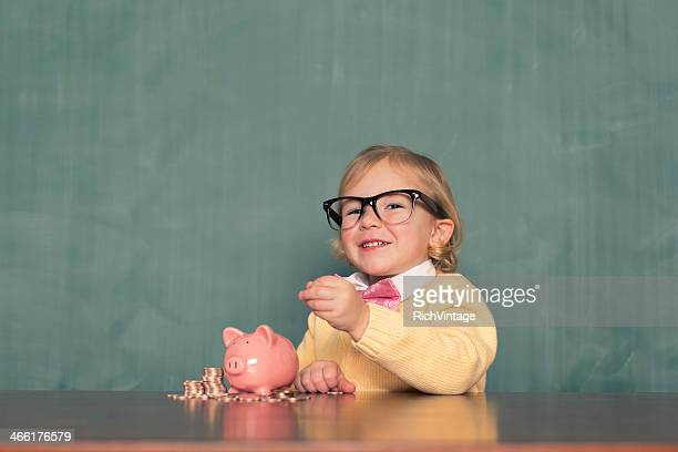 Junges Mädchen mit Brille spart Geld im Sparschwein