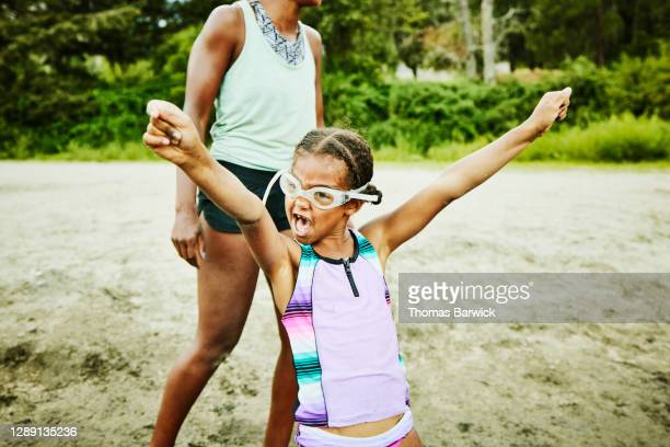young girl wearing goggles with arms raised playing at beach on summer afternoon - naughty america stock pictures, royalty-free photos & images