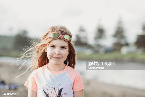 young girl wearing googles and rash guard at the beach - google stock pictures, royalty-free photos & images
