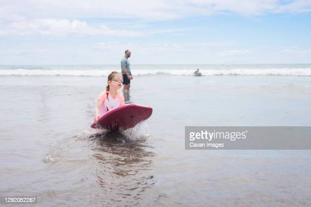 young girl wearing googles holding boogie board at the beach - google stock pictures, royalty-free photos & images