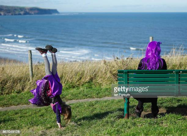 Young girl wearing goth clothing performs a handstand as her mother sits on a bench overlooking the harbour during the Whitby Goth Weekend on October...