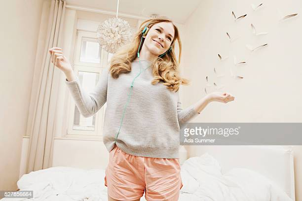 Young girl wearing headphones and dancing in her room