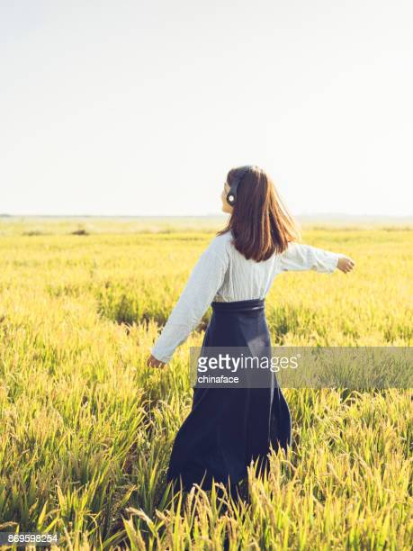 young girl wearing headphones dancing in field